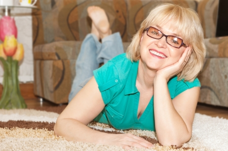 human age: Blonde woman with toothy smile lying on floor at home Stock Photo