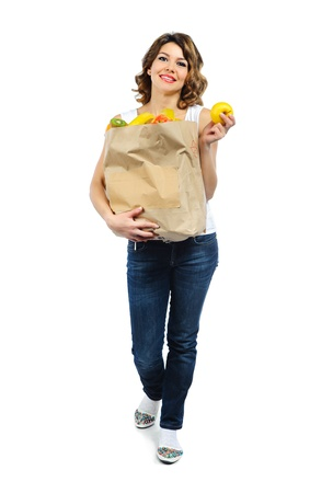 Young girl with fruits in paper bag isolated on white background photo