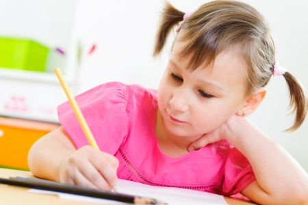Cute little girl drawing with colorful pencils at home photo