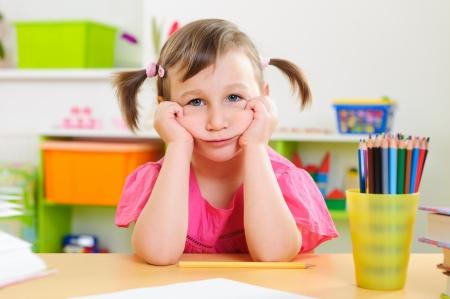bambini pensierosi: Upset bambina seduta con le matite colorate alla scrivania