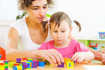 children playing together: Young mother and little daughter playing with colorful toy blocks