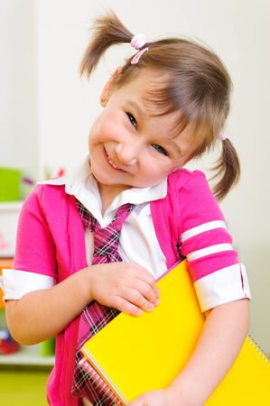 Cute shy girl with notebook folder standing in class photo