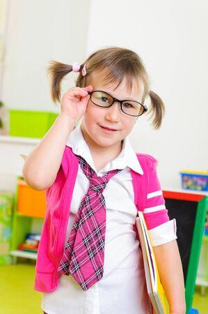 schoolgirl uniform: Cute little girl win eyeglasses and necktie with notebook folder