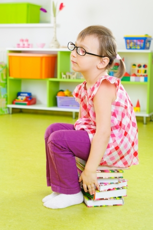 Tired little girl in glasses sitting on stack of books photo