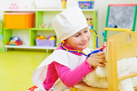 Cute little girl in medical uniform playing in doctor photo