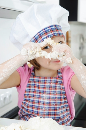 Little girl in hat and apron cooking in kitchen photo