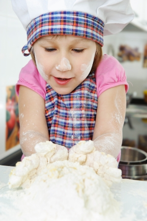 Little girl in hat and apron cooking in kitchen Stock Photo - 17789912