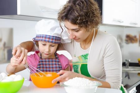Young mother with little daughter cooking cookies photo