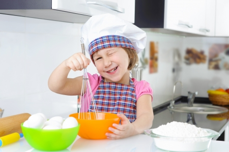 Cute little girl in hat and apron cooking cookies photo
