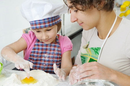 Young mother with little daughter cooking cookies Stock Photo - 17789915