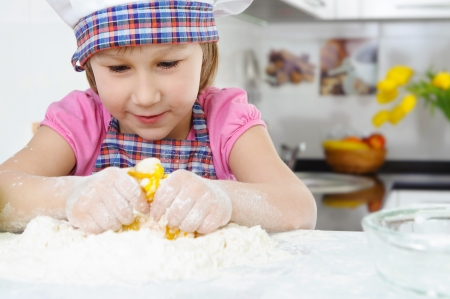 Cute little girl in hat and apron cooking cookies Stock Photo - 17789904