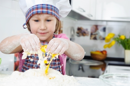 Cute little girl in hat and apron cooking cookies Stock Photo - 17789902