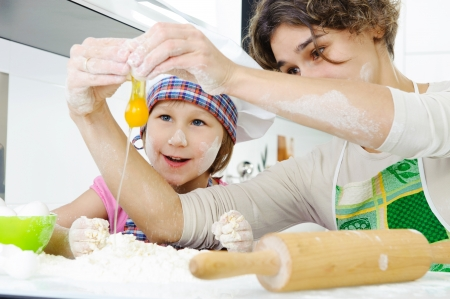 Young mother with little daughter cooking cookies Stock Photo - 17789894