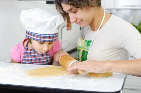 haciendo pan: Joven madre con hija pequeña masa de laminación para galletas