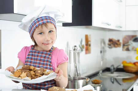 Cute little girl in apron holding plate with cookies photo
