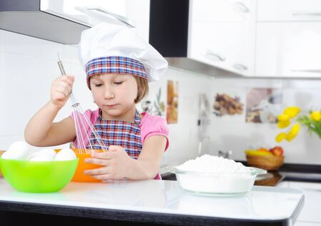 Cute little girl in hat and apron whisking eggs photo