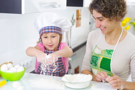 Sweet little girl sprinkle flour in kitchen Stock Photo - 17854470