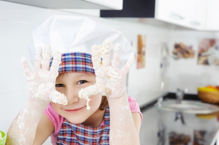 Little girl in hat and apron cooking in kitchen Stock Photo - 17854486