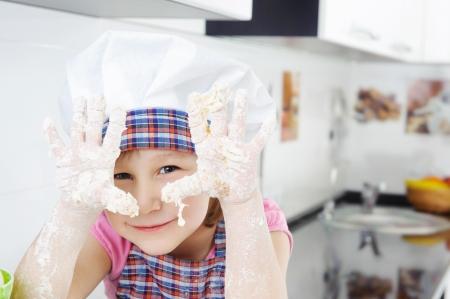haciendo pan: Niña con sombrero y delantal de cocina en la cocina Foto de archivo
