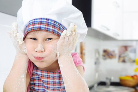 Funny little baker grimaces in the kitchen photo