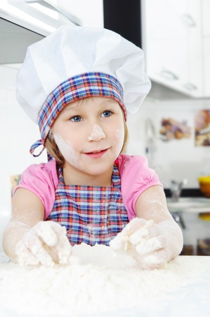 Cute little girl in hat and apron cooking cookies Stock Photo - 17854503