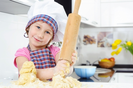 Beautiful little girl with rolling pin in kitchen Stock Photo - 17854474