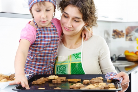 Little girl and young mother with baked cookies photo