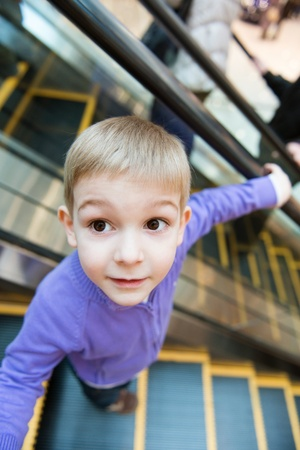 bajando escaleras: Chico lindo en la escalera mecánica en centro comercial Foto de archivo