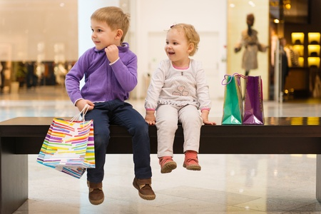 Little brother and sister with shopping bags sitting on bench in mall photo