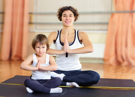 Young mother with little daughter exercising in gym photo