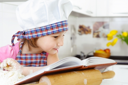 Little girl in baker hat and apron preparing cookies with cookbook photo