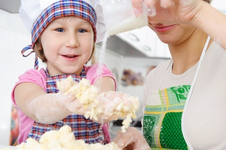 little dough: Little girl in baker hat and apron cooking in kitchen with mother