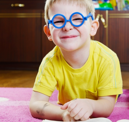 funy: Funy little boy in glasses lying on floor