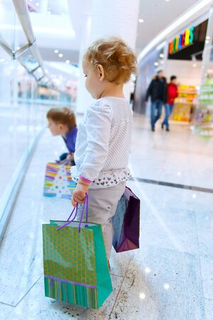 Two cute children with bags in mall photo