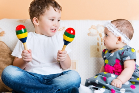 Cute little sister and her brother sitting with maracas on sofa Stock Photo