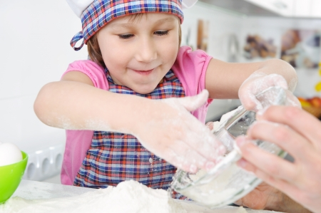 Cute little girl in hat and apron cooking cookies Stock Photo - 18203109