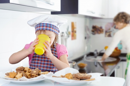 four person: Little cute girl drinking milk in kitchen