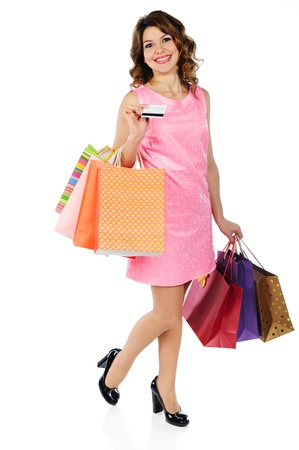 Beautiful young woman with credit card and shopping bags isolated on white background photo