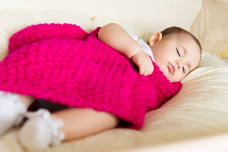 Closeup portrait of sleeping baby covered with knitted blanket photo