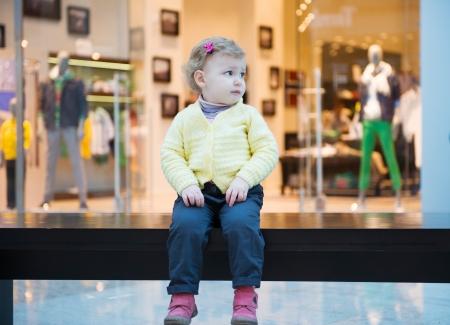 Verstoord beetje verloren meisje zittend op bankje in winkelcentrum Stockfoto