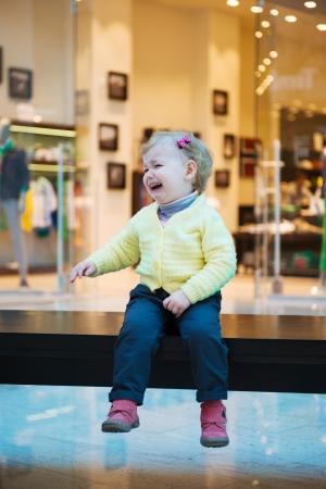 fille pleure: Boulevers� peu fille perdue assis sur un banc dans un centre commercial Banque d'images