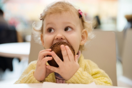 Cute little girl eating muffins in cafe photo