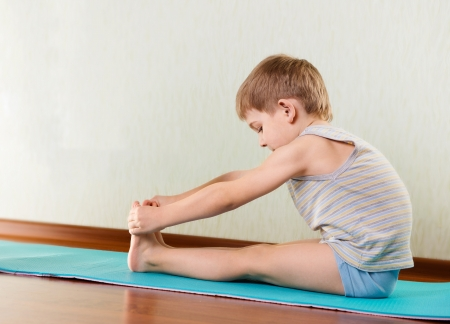 Concentrated little boy exercising and stretching in gym