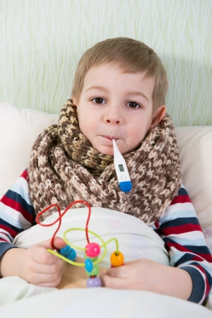 Sick little boy lying in bed with thermometer in mouth photo