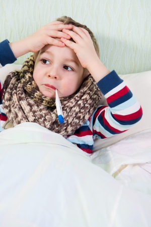 Sick little boy lying in bed with thermometer in mouth Stock Photo - 18468101