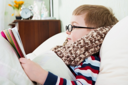 grippe: Sick little boy in glasses lying in bed with book
