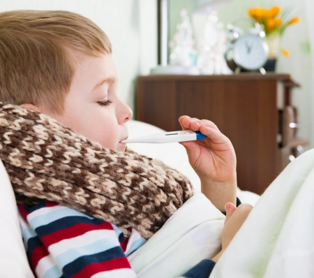 Sick little boy lying in bed with thermometer in mouth Stock Photo - 18576680