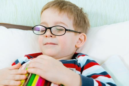 Little tired boy in glasses sleeping with book in bed photo