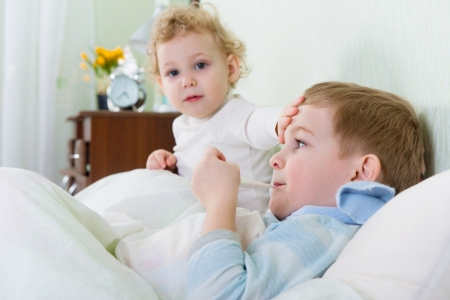 brother sister: Little girl and her sick brother lying in bed at home