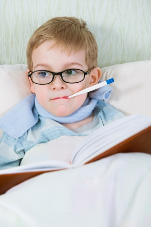 Sick little boy lying in bed with thermometer and reading book photo